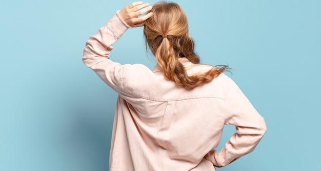 Jolie femme blonde se sentir désemparée et confuse, pensant à une solution, avec la main sur la hanche et d'autres sur la tête, vue arrière