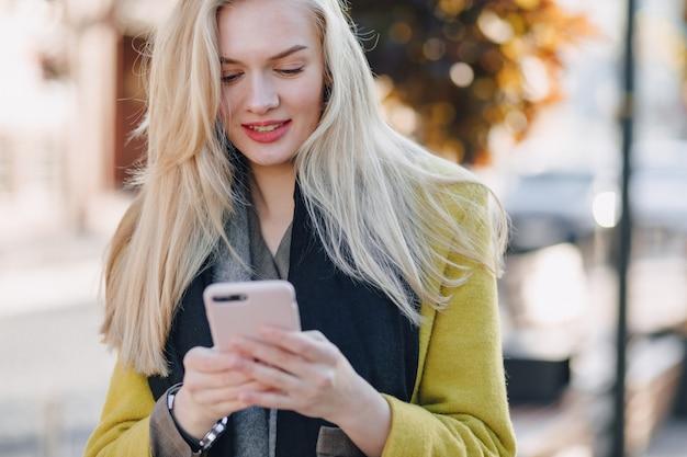Jolie femme blonde séduisante émotionnelle en manteau avec smartphone marche dans la rue de la ville. communication pendant la marche, le mode de vie, la rue.