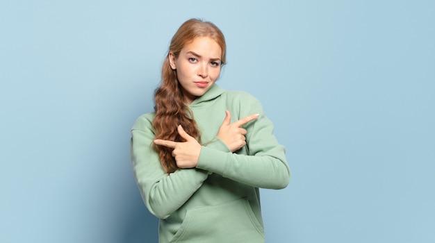Jolie femme blonde semblant perplexe et confuse, peu sûre et pointant dans des directions opposées avec des doutes