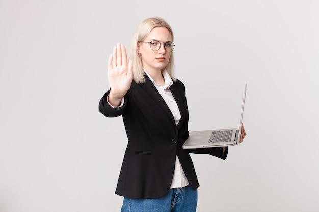 Jolie femme blonde à la sérieuse montrant la paume ouverte faisant un geste d'arrêt et tenant un ordinateur portable