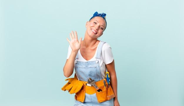 Jolie femme blonde souriant joyeusement, agitant la main, vous accueillant et vous saluant et réparant le concept de maison
