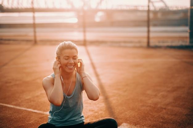 Jolie femme blonde souriante caucasienne assise sur la cour le matin avec des écouteurs dans les oreilles et écouter de la musique.