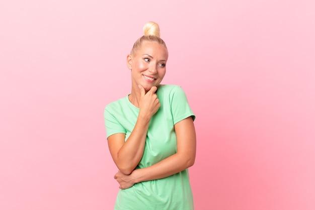 Jolie femme blonde souriante avec une expression heureuse et confiante avec la main sur le menton