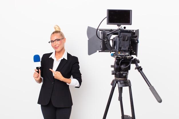 Jolie femme blonde souriante joyeusement, se sentant heureuse et pointant sur le côté et tenant un micro. concept de présentateur