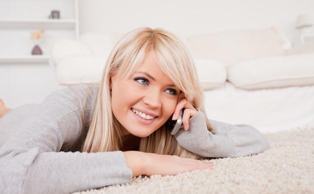 Jolie femme blonde souriante parlant au téléphone cellulaire couchée sur un tapis