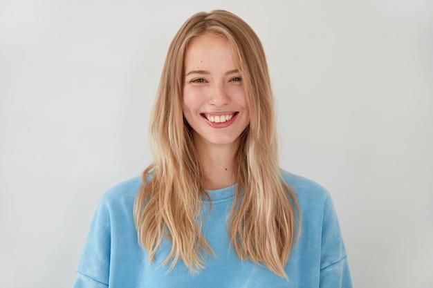Jolie femme blonde souriante avec un regard tendre attrayant, a une expression joyeuse