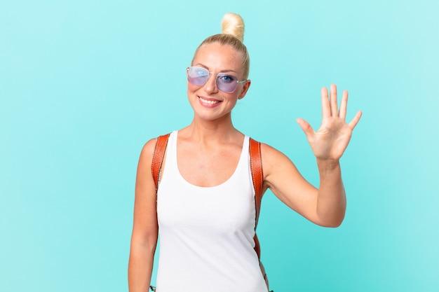 Jolie femme blonde souriante et semblant amicale, montrant le numéro cinq. concept d'été