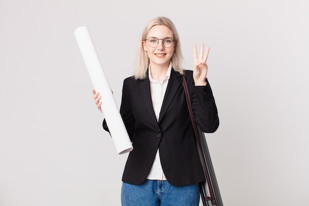 Jolie femme blonde souriante et semblant amicale, montrant le numéro trois. concept d'architecte