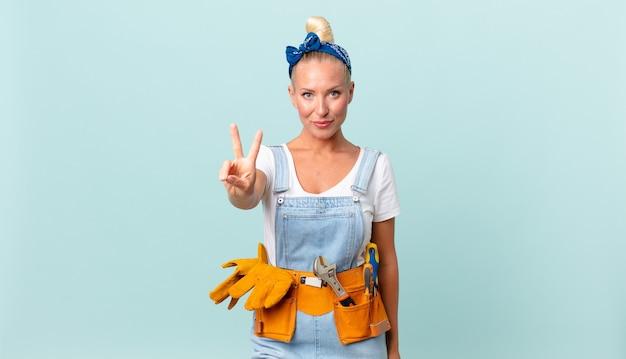 Jolie femme blonde souriante et semblant heureuse, gesticulant la victoire ou la paix et réparant le concept de maison
