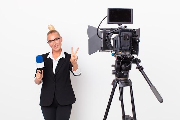 Jolie femme blonde souriante et semblant heureuse, gesticulant la victoire ou la paix et tenant un micro. concept de présentateur