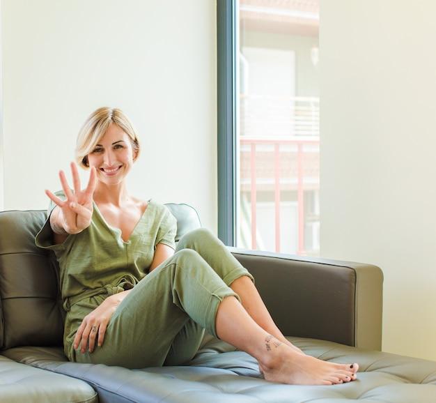 Jolie femme blonde souriante et à la sympathique, montrant le numéro quatre ou quatrième avec la main vers l'avant, compte à rebours