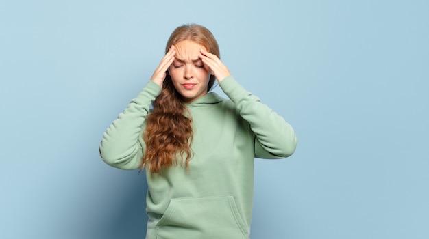 Jolie femme blonde à la stress et frustré, travaillant sous pression avec un mal de tête et troublé par des problèmes