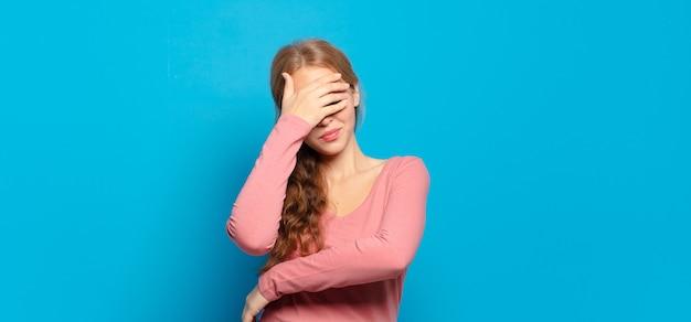 Jolie femme blonde à la stress, honte ou contrarié, avec un mal de tête, couvrant le visage avec la main