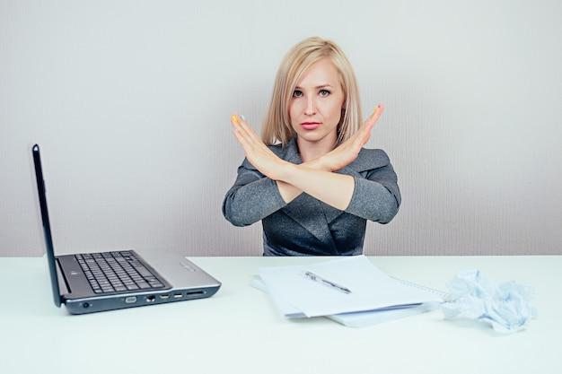Jolie femme blonde stricte (femme d'affaires) en costume d'affaires élégant montre un arrêt de geste de la main ( non ) avec un ordinateur portable et un tas de dossiers dans le bureau du lieu de travail
