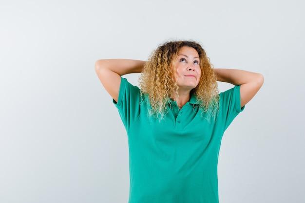 Jolie femme blonde en t-shirt de polo vert, gardant les mains derrière la tête et regardant pensif, vue de face.