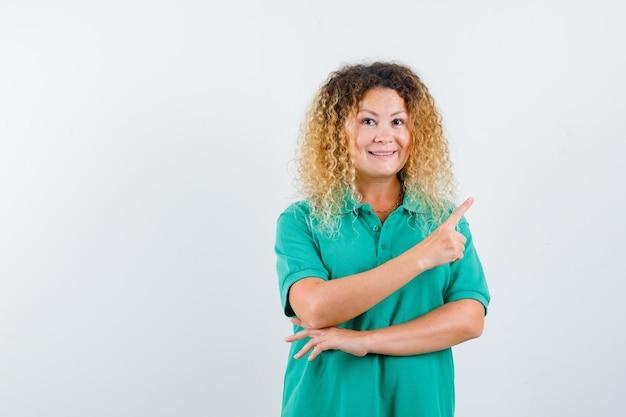 Jolie femme blonde en t-shirt de polo vert pointant vers le coin supérieur droit et à la vue de face, joyeuse.