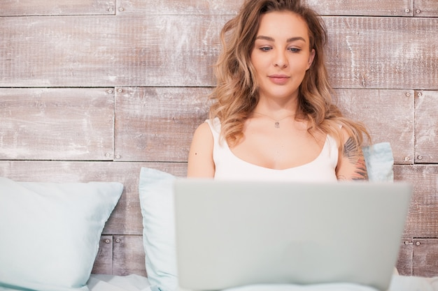 Jolie femme blonde travaillant tard dans la nuit sur son ordinateur portable en pyjama.