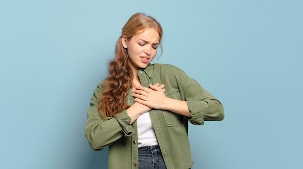 Jolie femme blonde à la triste, blessée et le cœur brisé, tenant les deux mains près du cœur, pleurant et se sentant déprimé