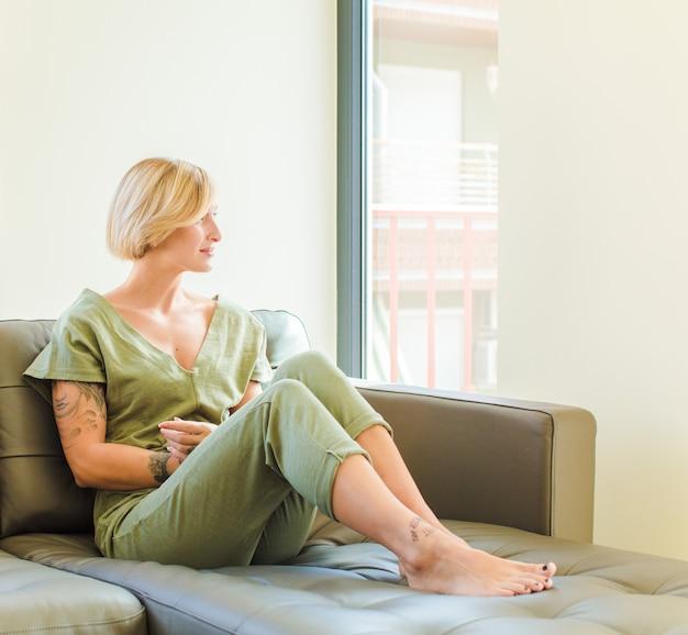 Jolie femme blonde sur la vue de profil à la recherche de copier l'espace à venir, penser, imaginer ou rêver