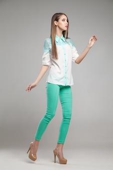 Jolie femme en blouse blanche et pantalon turquoise posant au studio