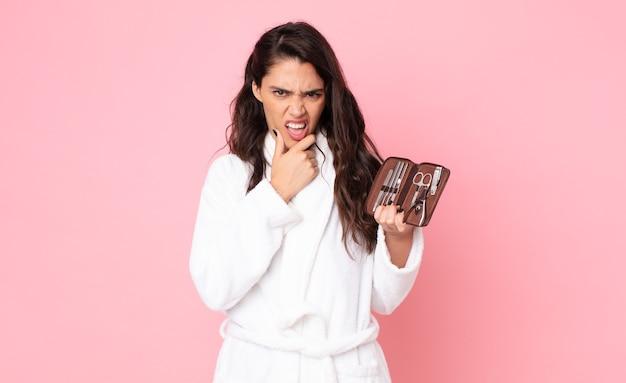 Jolie femme avec la bouche et les yeux grands ouverts et la main sur le menton et tenant un sac de maquillage avec des outils à ongles