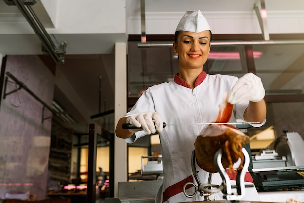 Jolie femme boucherie coupant du jambon avec un couteau.