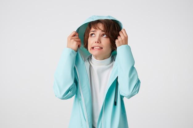 Jolie femme bouclée aux cheveux courts dégoûtante en golf blanc et manteau de pluie bleu clair, se cachant sous le capot de la pluie et regardant sur le côté gauche, se dresse sur fond blanc.