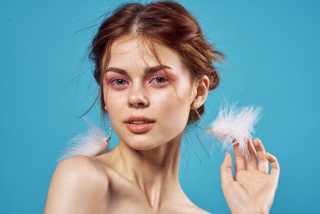 Jolie femme boucles d'oreilles épaules nues maquillage fraîcheur bleu.