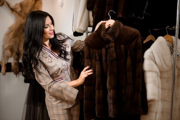 Jolie femme en boutique de manteau de fourrure avec un manteau de fourrure sur le cintre