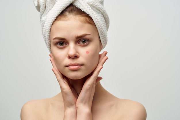 Jolie femme avec un bouton sur le studio de cosmétologie du visage