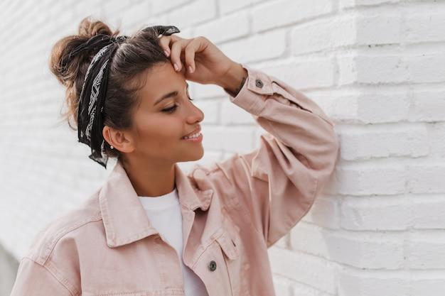 Jolie femme bronzée avec chignon et sourires de bandeau