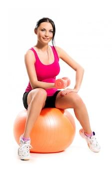 Jolie femme brune assise sur le ballon