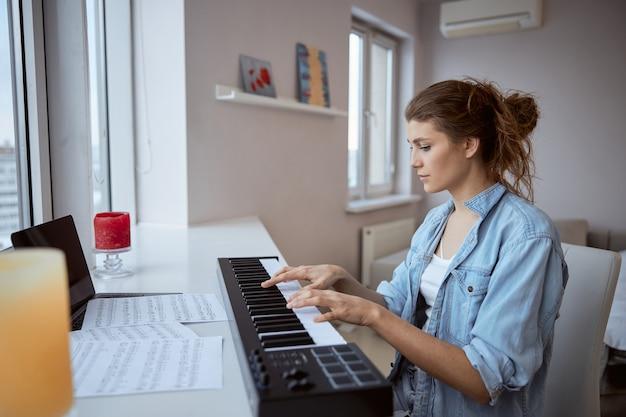 Jolie femme brune assise dans sa chambre en jouant du synthétiseur