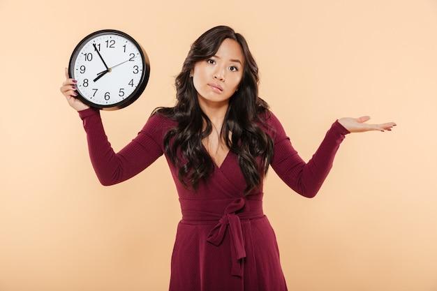 Jolie femme brune aux cheveux longs bouclés tenant une horloge montrant près de 8 étant en retard ou manquant quelque chose jetant la main sur fond de pêche