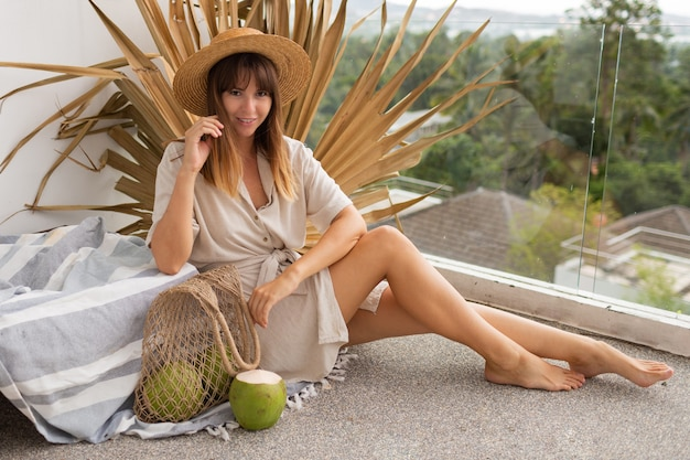 Jolie femme brune en chapeau de paille et robe en lin posant sur une terrasse sur une feuille de palmier sèche. noix de coco fraîches.