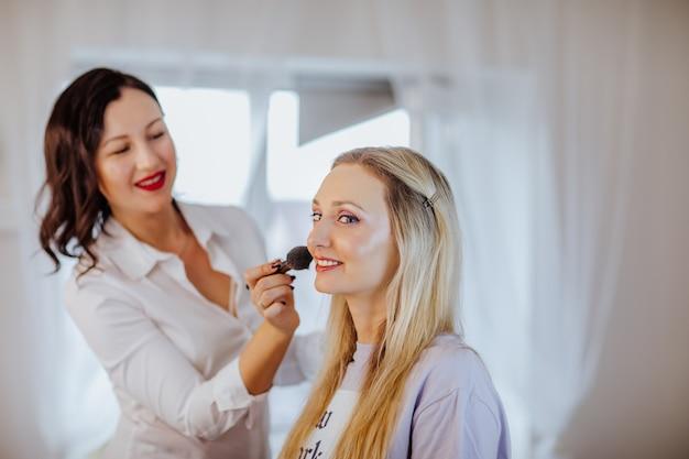 Jolie femme brune en chemise blanche avec des lèvres rouges qui composent un modèle blond dans son armoire.