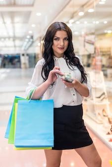 Jolie femme brune comptant des dollars sur les achats