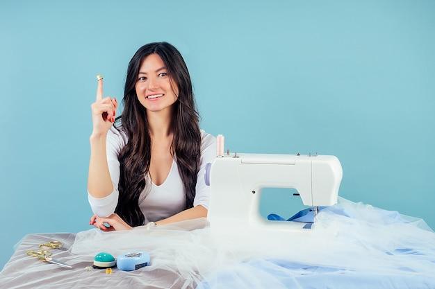 Jolie femme brune couturière tailleur (couturière) dé à coudre sur le doigt pointant vers le haut derrière la table avec machine à coudre sur fond bleu dans le studio.