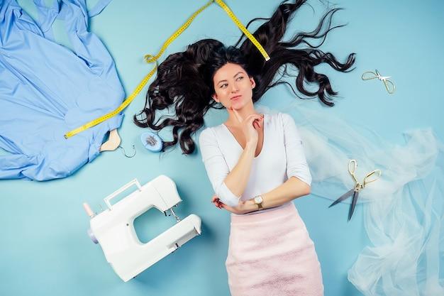 Jolie femme brune couturière tailleur (couturière) rêve et pense à une nouvelle collection de vêtements sur le sol avec machine à coudre et ruban à mesurer sur fond bleu dans le studio.