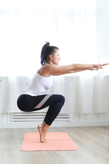 Jolie femme brune, faire du yoga à la maison.