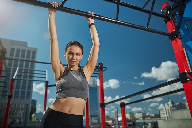 Jolie femme brune gardant les mains sur la barre horizontale tout en allant faire de l'exercice le matin