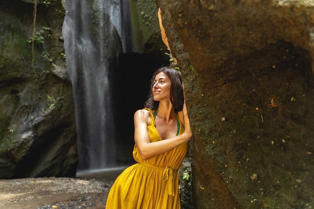 Jolie femme brune gardant le sourire sur son visage, cascade pittoresque en arrière-plan