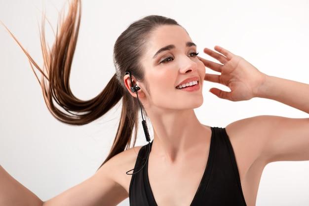 Jolie femme brune en jogging haut noir, écouter de la musique sur des écouteurs posant isolé sur une coiffure de queue de cheval mur blanc en agitant les cheveux longs