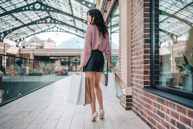 Jolie femme brune à longues jambes en pull tricoté confortable, jupe courte en cuir et talons hauts, marchant dans un centre commercial avec un tas de sacs en papier dans les mains
