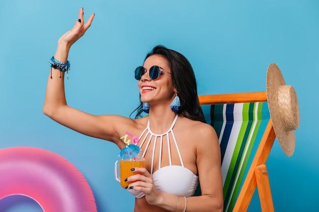 Jolie femme brune à lunettes de soleil en agitant la main avec le sourire