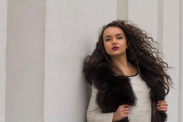 Jolie femme brune en manteau de fourrure noir posant sur le mur blanc
