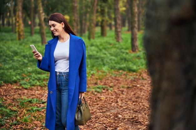 Jolie femme brune marchant dans le parc