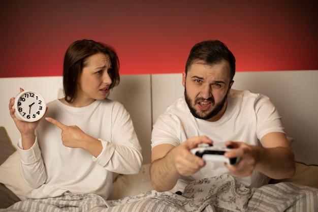 Jolie femme brune montre l'horloge pendant que son petit ami barbu joue à la console de jeux