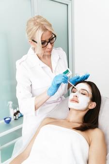 Jolie femme brune obtenant une procédure cosmétique par un spécialiste en position couchée dans un salon de beauté