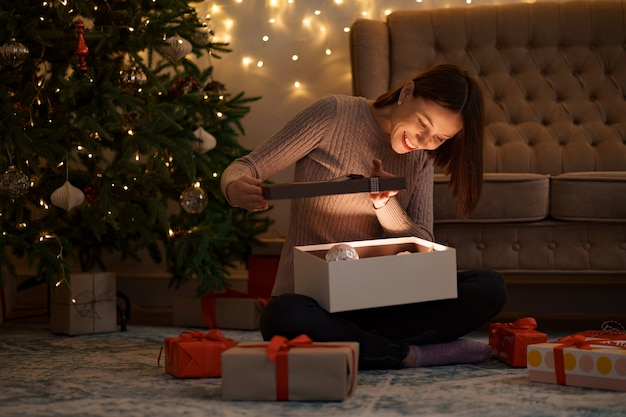 Jolie femme brune ouvre un adorable cadeau avec des lumières